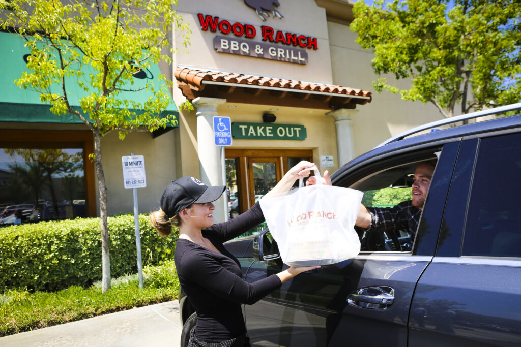 team member handing off food to a guest in a car