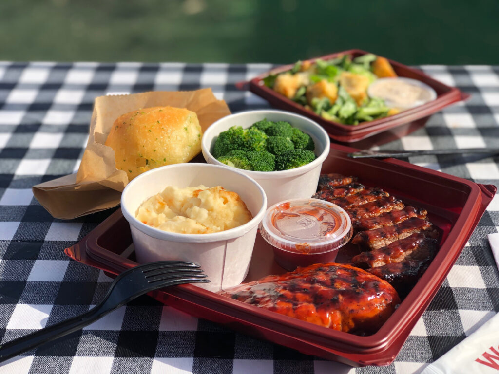 individually packaged catering meal with meat, sides, bread, utensils and napkin