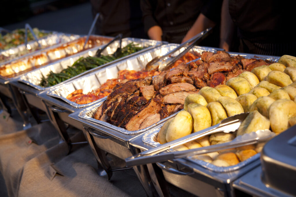 Rolls, tri tip, chicken and breast with various side dishes on a buffet line in chafing dishes.